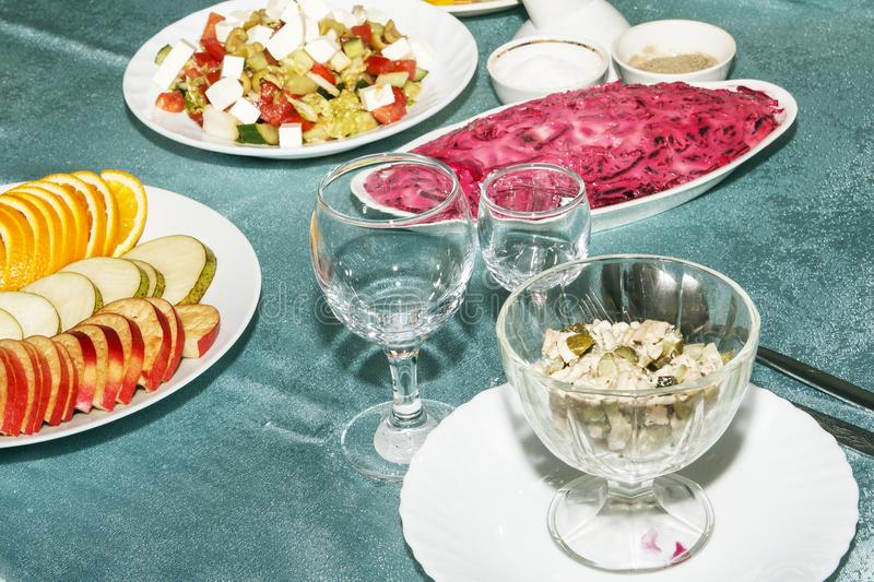Banquet table with cold snack in restaurant for reception. Sliced fresh vegetables and fruit closeup. Empty stemware for drink. Si. De view stock photography