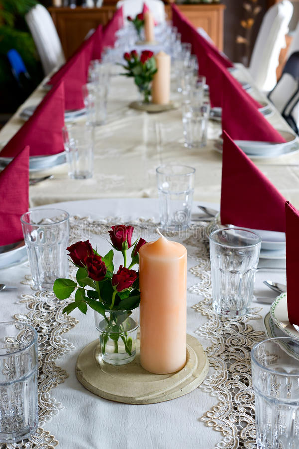 Banquet table setting themed with roses. Beautiful banquet setting at a long table themed with peach colored candles and red roses stock photos