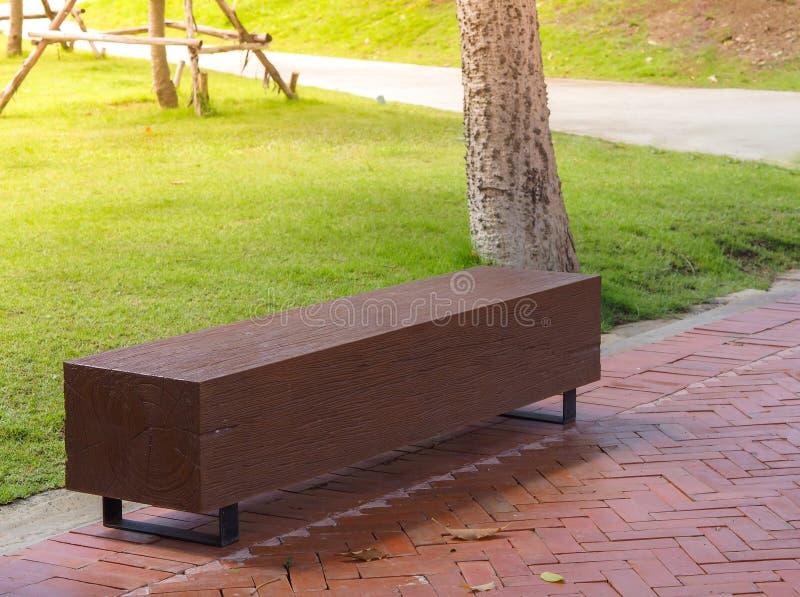 Banquillo de madera color marrón en el jardín camino de parque público imagen de archivo