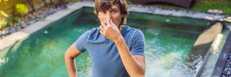 BANRET ung man för LÅNGT FORMAT med avsmak på hans framsidarazzianäsa, något stinker, den mycket dåliga lukten i simbassäng royaltyfri bild