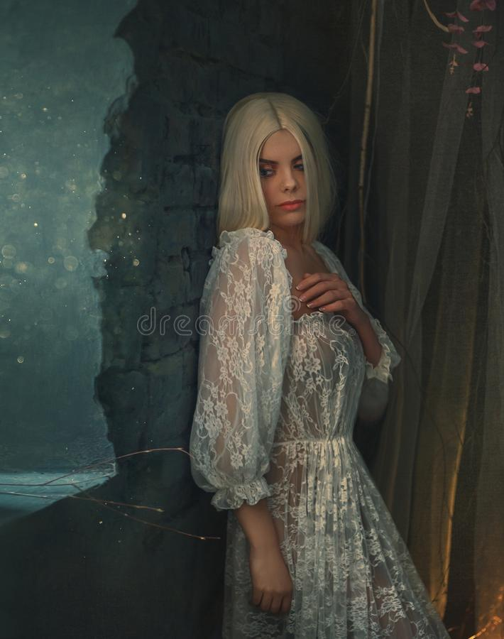 Free Banshee Fairy. Pale Blonde Girl In White Vintage Dress. Seductive Princess, With Sexy, Long Legs Posing Against The Stock Image - 115529901
