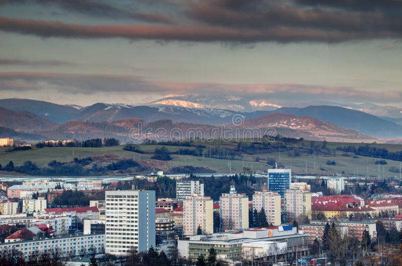 Banska Bystrica tower blocks and snowy Low Tatra range Slovakia. Row of socialist era tower blocks and houses in Banska Bystrica outskirts with snow-capped stock photography