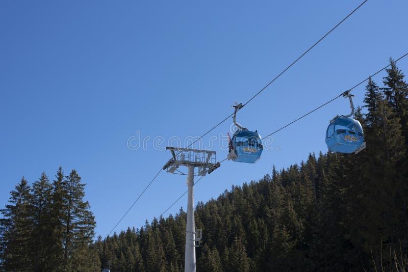 Bansko, Болгария, 3-ье апреля 2018: Панорама лыжного курорта Bansko с кабиной подъема лыжи, зелеными горами стоковое фото