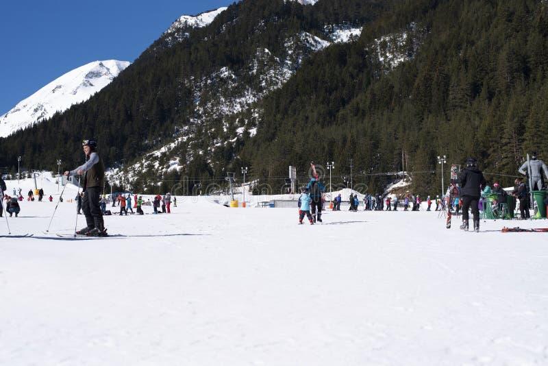 Bansko, Bulgarije, 03 April, 2018: De post van de Banskoski, Kolarski-skilift bij Banderishka-polyana, skiërs op skihellingen, be stock fotografie