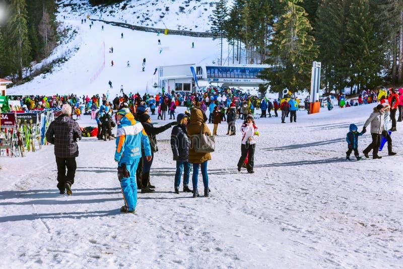 Bansko ski resort, ski lift and people on slope, Bulgaria. Bansko, Bulgaria - December 16, 2017: Kolarski ski lift at Banderishka polyana, skiers on ski slopes royalty free stock photography