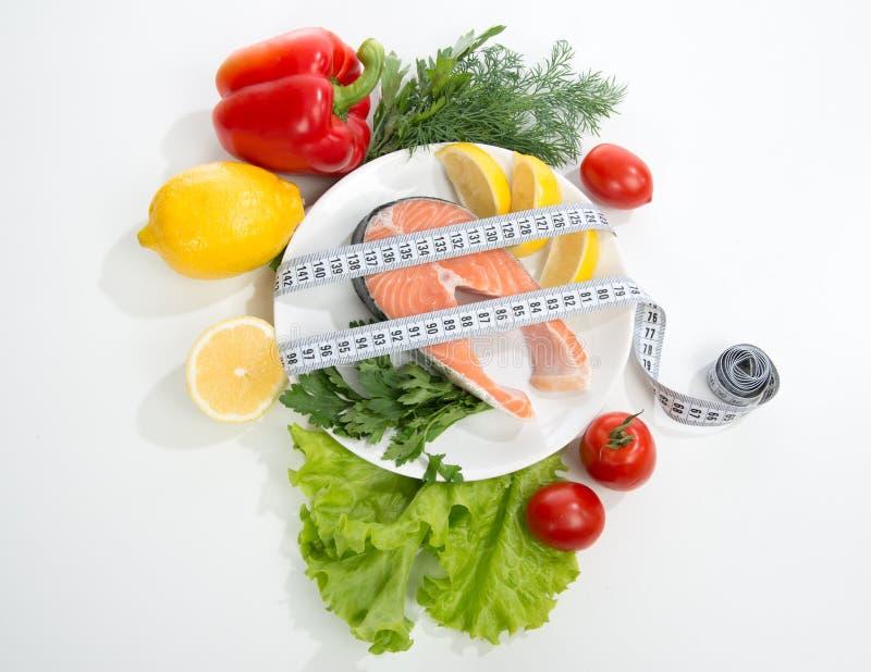 Banta begreppet för viktförlust Ny laxbiff för lunch med måttband centimetr ny laxsteak royaltyfri fotografi