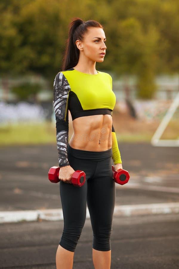 Banta den idrotts- kvinnan med hantlar i stadion Sportig sexig flicka med plan bukgenomkörare, utomhus royaltyfria bilder