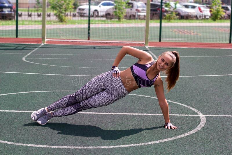 Banta den idrotts- kvinnan som gör plankövning på basketdomstolen royaltyfri foto