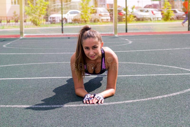 Banta den idrotts- kvinnan som gör plankövning på basketdomstolen arkivbild