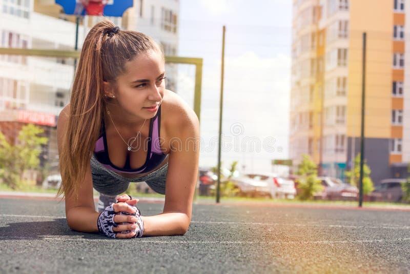 Banta den idrotts- kvinnan som gör plankövning på basketdomstolen royaltyfria foton