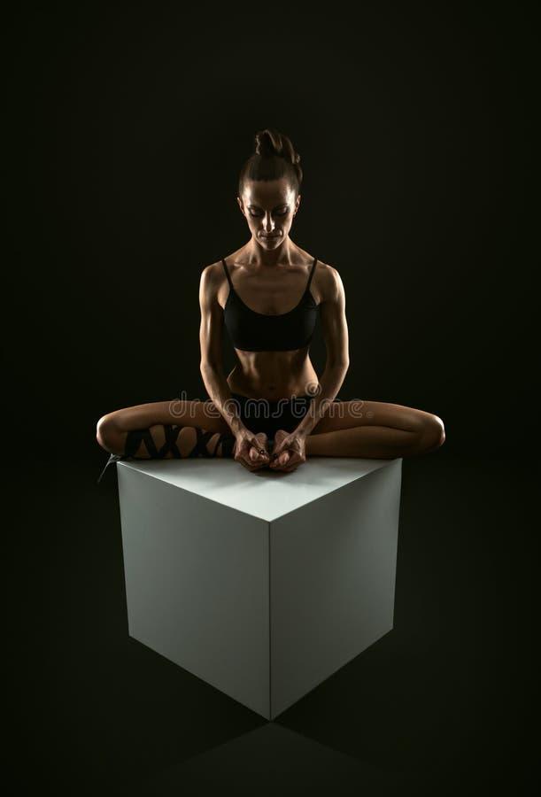 Banta den idrotts- kvinnan som gör sträcka yogaövning arkivbilder