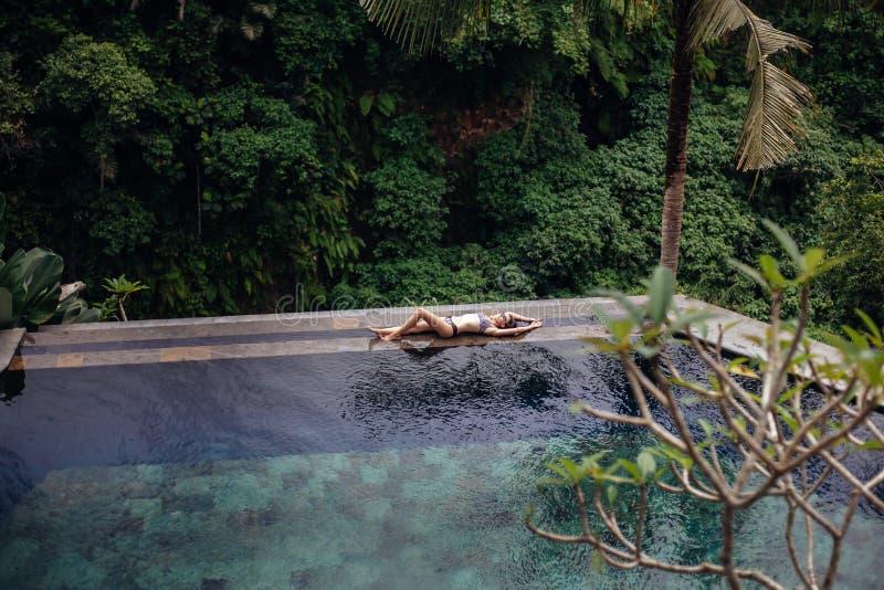 Banta den sexiga brunettkvinnan i baddräkt som kopplar av på tropisk oändlighetspöl för kant i djungel Gömma i handflatan omkring arkivbilder