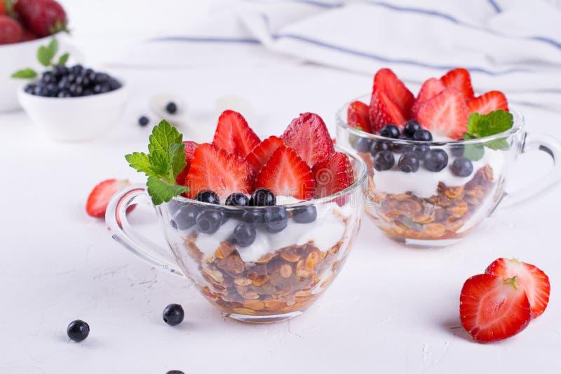 Banta den sunda efterrätten med yoghurt, granola och nya bär royaltyfri fotografi