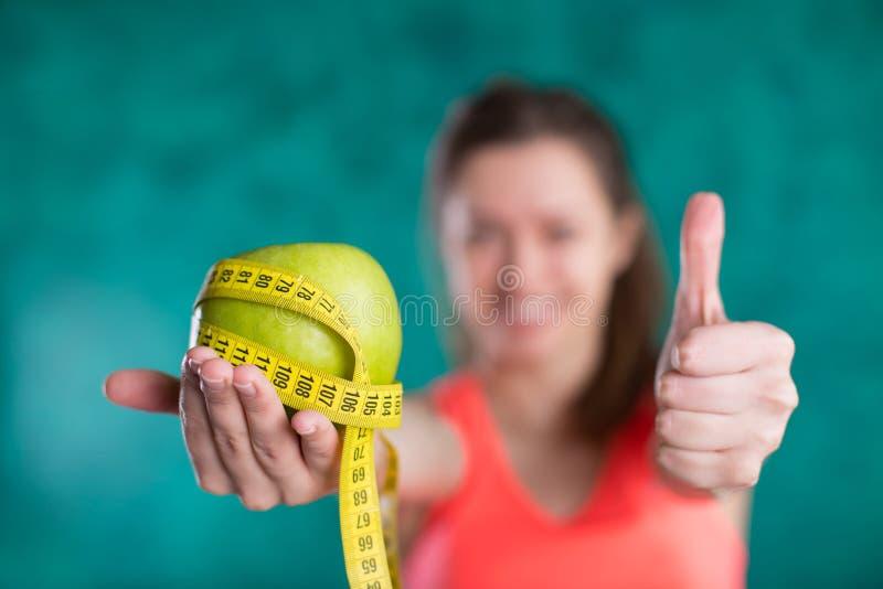 banta Den sunda lyckliga kvinnlign med äpplet och måttbandet för bantar och begreppet för viktförlust - som isoleras på turkosbak royaltyfri fotografi