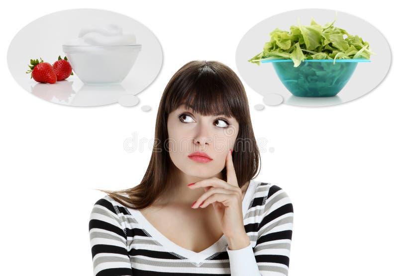 Banta, den unga kvinnan som väljer mellan frukter, och sötsaker. väga los arkivfoto