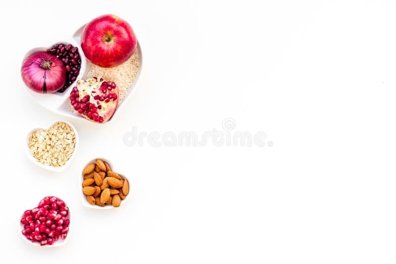 Banta för sund hjärta Mat med antioxidants Grönsaker frukter, muttrar i hjärta formad bunke på den vita bakgrundsöverkanten arkivfoton