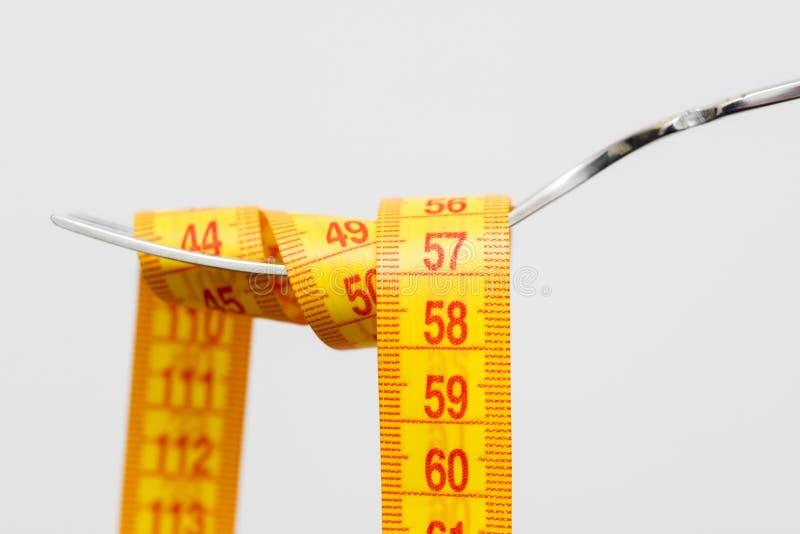 Banta för viktförlust och att mäta bandet med gaffeln för tar omsorg sunt ätabegrepp royaltyfria foton