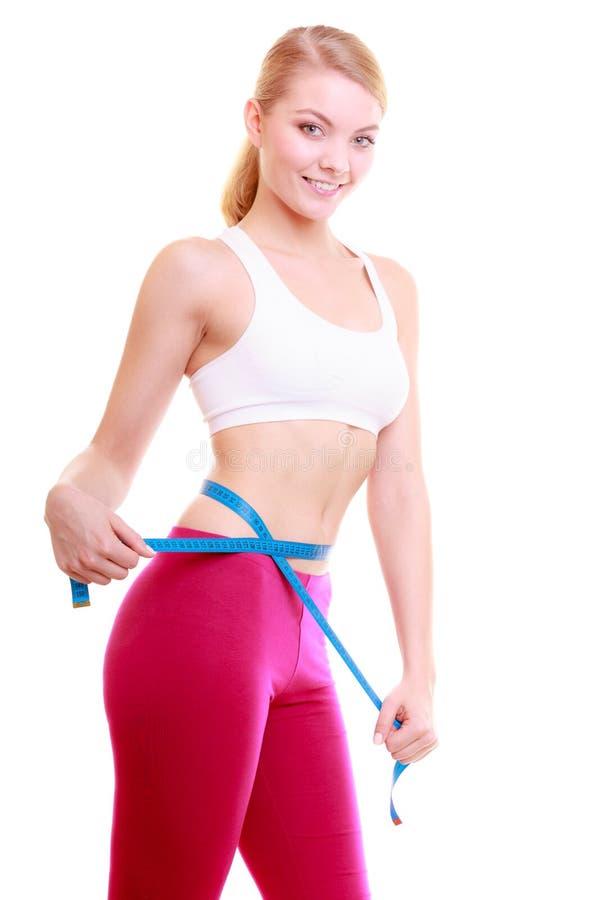 Banta. Flicka för konditionkvinnapassform med måttbandet som mäter hennes midja royaltyfri foto