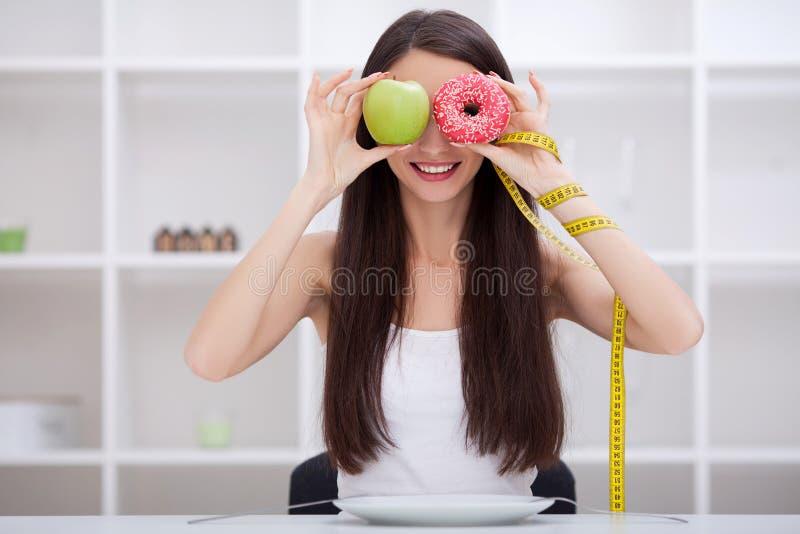 banta Härlig ung kvinna som väljer mellan frukt- och skräpfooen royaltyfri bild
