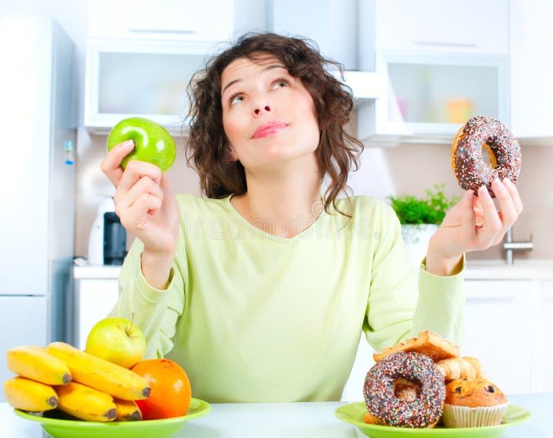 Banta. Kvinna som väljer mellan frukter och sötsaker arkivfoton