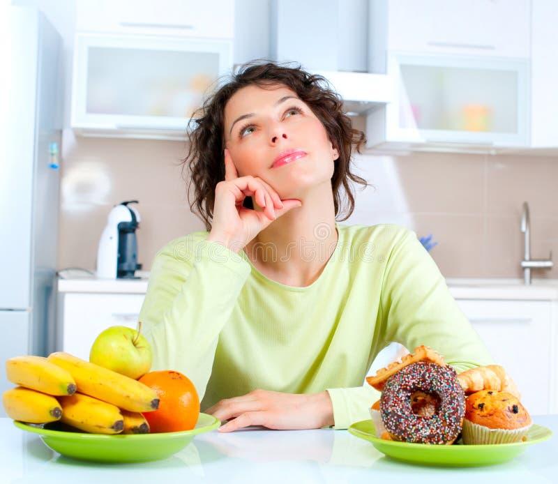 Banta. Kvinna som väljer mellan frukter och sötsaker arkivbilder