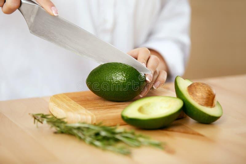 banta Kvinnlign räcker den bitande avokadot i kök arkivfoton