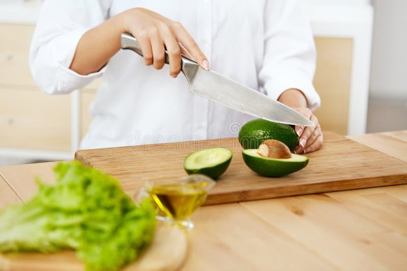 banta Kvinnlign räcker den bitande avokadot i kök royaltyfria bilder