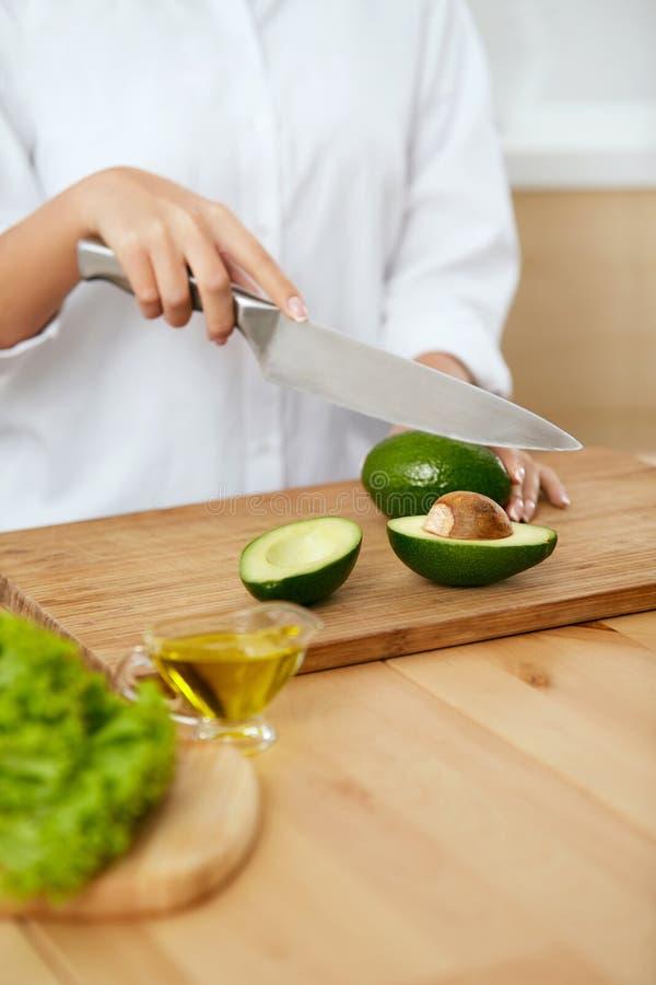 banta Kvinnlign räcker den bitande avokadot i kök arkivfoto