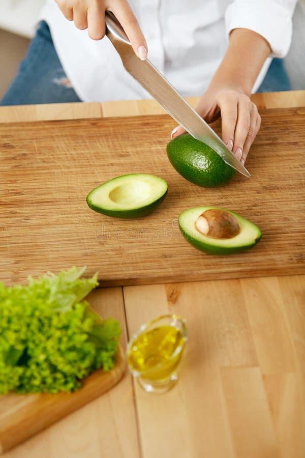 banta Kvinnlign räcker den bitande avokadot i kök arkivbild