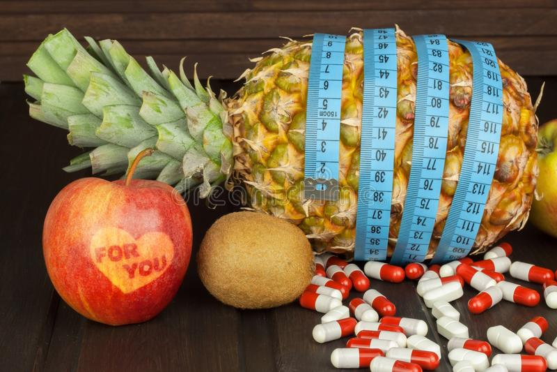 banta mat Mogen ananas och mätaband på en träbakgrund Preventivpillerar och diet-tillägg För dig royaltyfria foton