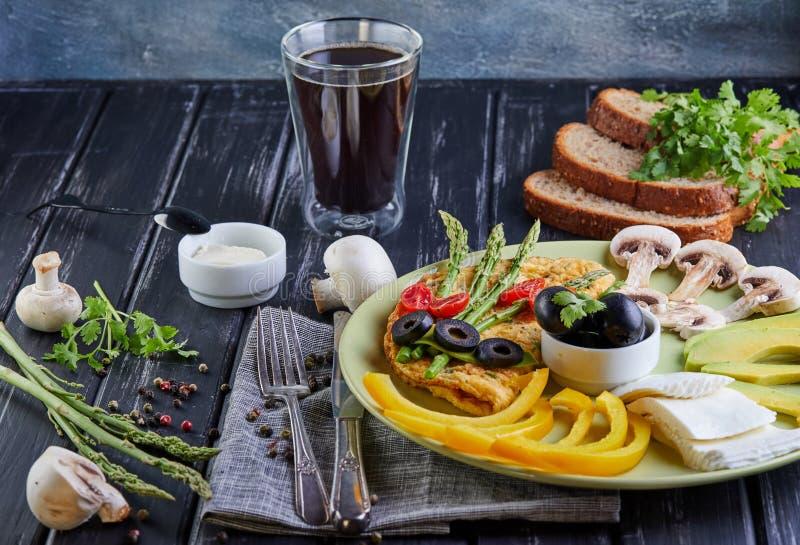 Banta menyn Sunt banta frukostgrönsaker på en platta - förvanskade ägg, avokadot, spansk peppar, sherrytomater, oliv som är nya arkivbilder