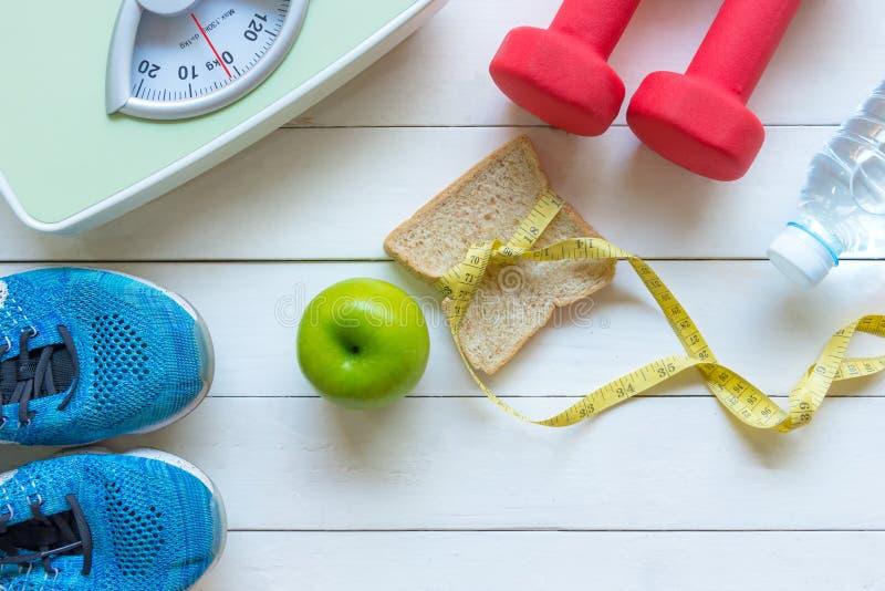 Banta och det sunda begreppet f?r livf?rlustvikt Gr?nt ?pple och klapp f?r viktskalam?tt med den nya gr?nsaken och sportutrustnin arkivbilder