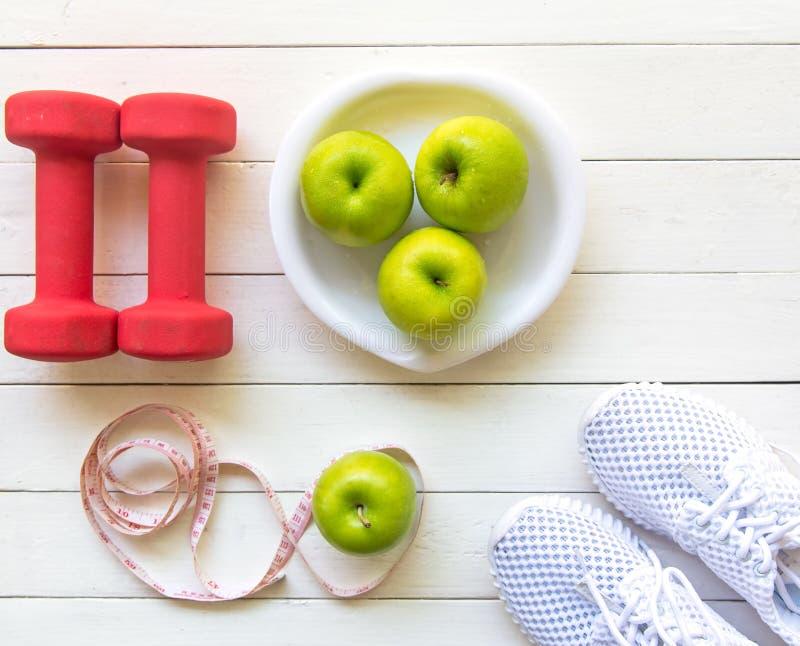 Banta och viktförlust för sund omsorg med konditionutrustning, sötvatten och bära frukt sunt, äpplet - grönt äpple, på vit träbac arkivbild