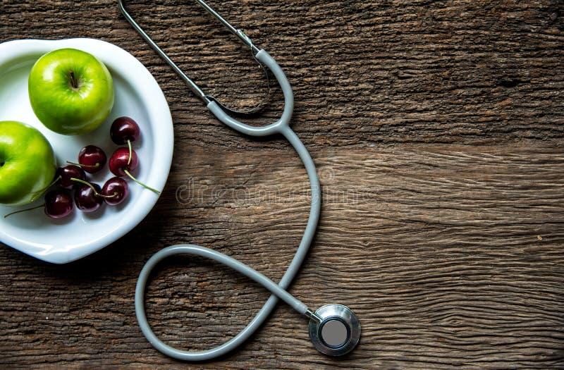 Banta och viktförlust med att mäta klappet och göra grön äpplet på bästa sikt för träbakgrund royaltyfria foton