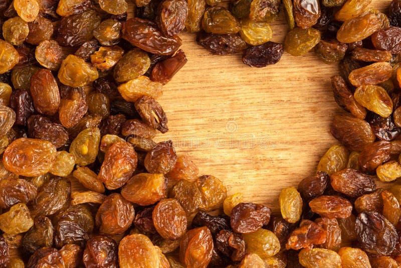 Banta sund mat. Gräns av russinet på träbakgrund arkivfoto
