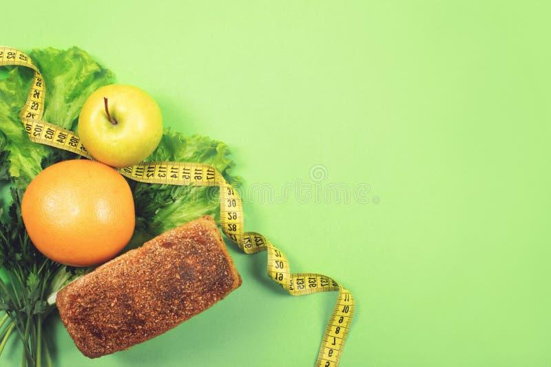 Banta, väg förlust, sunt äta, begrepp för ny mat Hela kornbröd för sund mat, grönsaker, frukter och gräsplaner, örter med arkivbilder