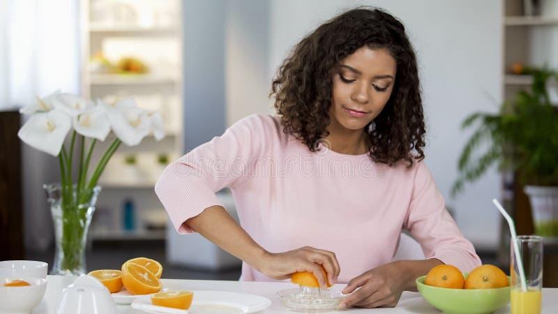 Bantar den unga kvinnan för det blandade loppet som pressar orange fruktsaft, vikt och vård- kontroll, arkivfoton