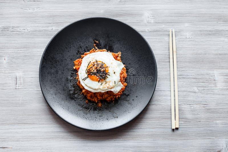 Bap de bokkeum de Kimchi de plat noir et de baguettes image stock