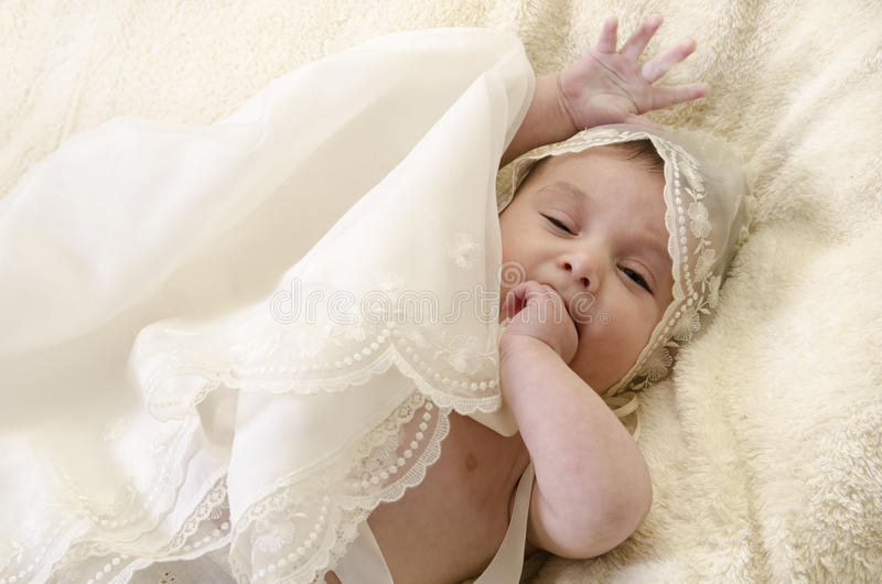 Baptism clothes and little baby. Baby with ceremonial clothes biting her hand royalty free stock photography