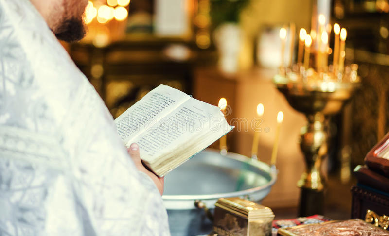 Baptism priest reading from bible during ceremony holding cross. royalty free stock images