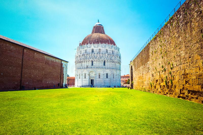 Baptistery of St. John on Square of Miracles with brick wall, famous Leaning tower of Pisa with green lawn in Pisa, Tuscany, Italy stock photography