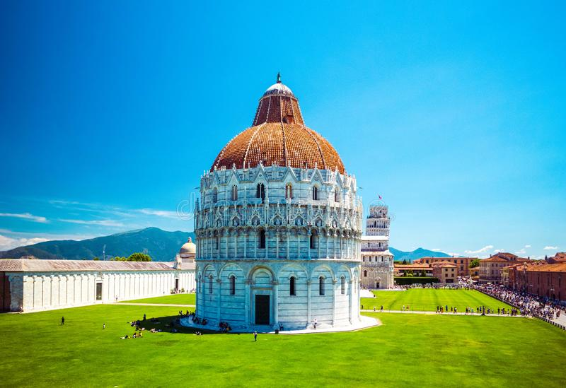 Baptistery of St. John on Square of Miracles, Leaning Tower, famous inclined tower of Pisa with green lawn in Pisa, Tuscany, Italy stock photos