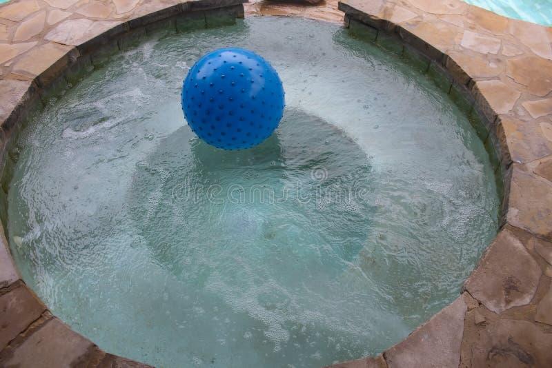 Baquet chaud rond construit de la pierre avec de l'eau pétillant et d'une boule flottant dans elle photos libres de droits