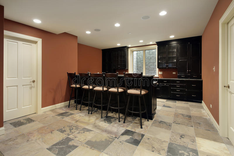 Bar in basement with dark wood cabinetry. Bar in basement of luxury home with dark wood cabinetry stock image