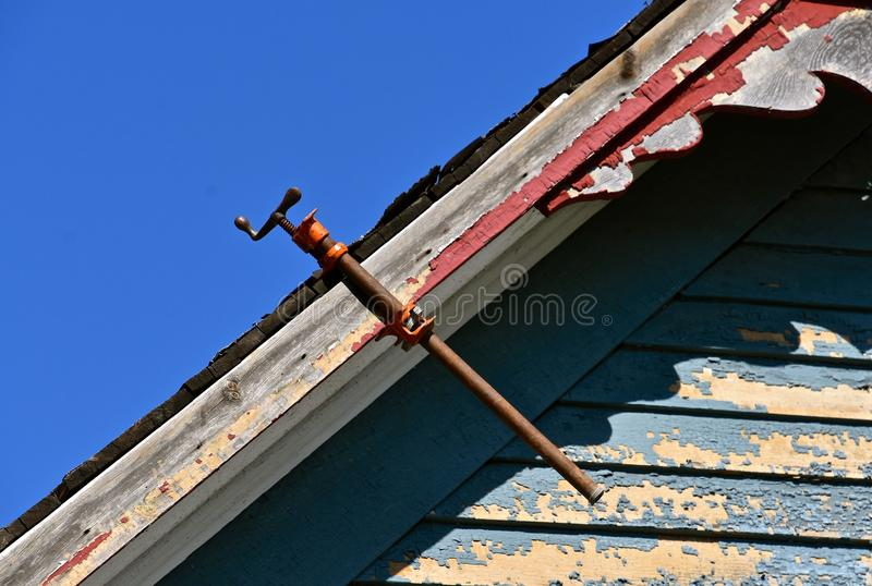 Bar clamps used to glue facia board on old house. A bar clamp is used to glue a broken facia board on an old house with peeling paint stock images