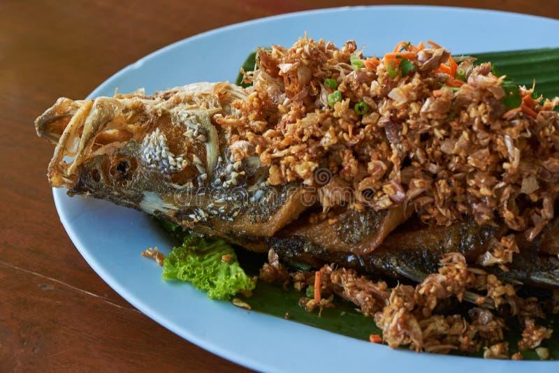 Bar de mer frit avec le poivre d'ail du plat bleu images libres de droits