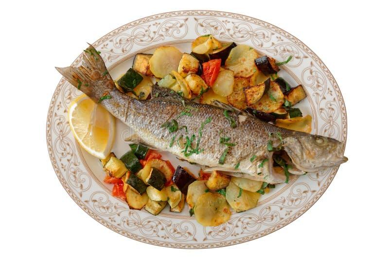 Bar de mer grillé avec les légumes cuits au four d'isolement sur le blanc photographie stock