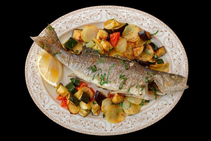 Bar de mer grillé avec les légumes cuits au four d'isolement sur le noir image stock