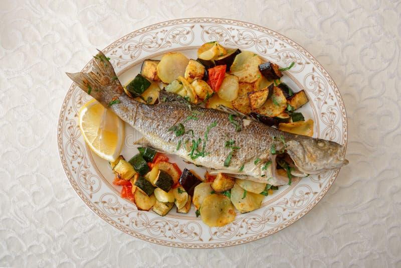 Bar de mer grillé avec les légumes cuits au four photo libre de droits