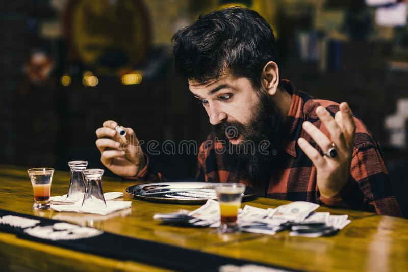 Bar drinking. shocked man at table with alcohol drinks, money stock photography
